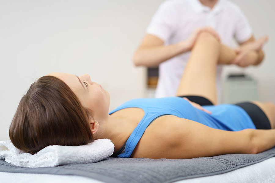 Physio examining woman's knee
