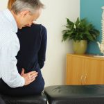 Brighton chiropractor examines back