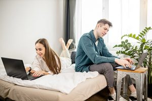 couple on bed on laptops