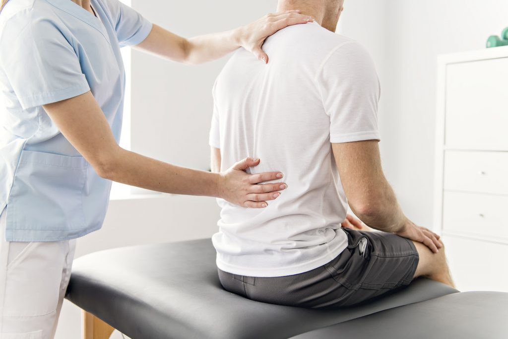 Physio examines a seated patient's back